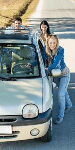 Три молодых человека подталкивают автомобиль, лишние трудовые ресурсы, чтобы ускорить работу